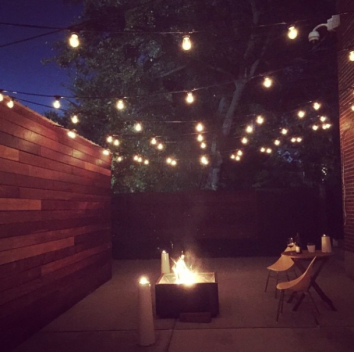 dwell-outdoor-backyard-string-lights-fireplace